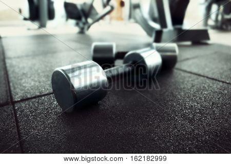Pair of dumbbells on floor in gym