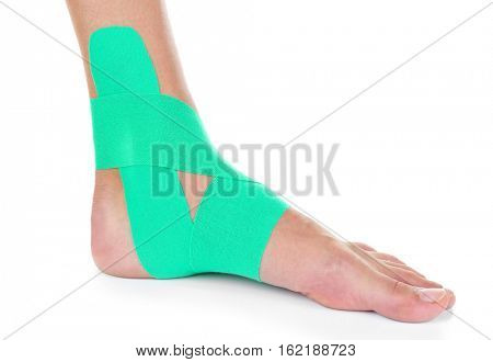 Female foot with physio tape on white background