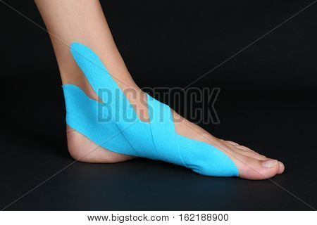 Female foot with physio tape on black background