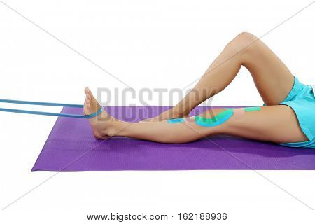Woman with physio tape doing exercise on white background