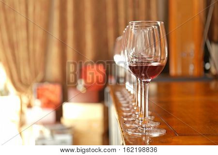 Row of glasses with red wine on bar counter