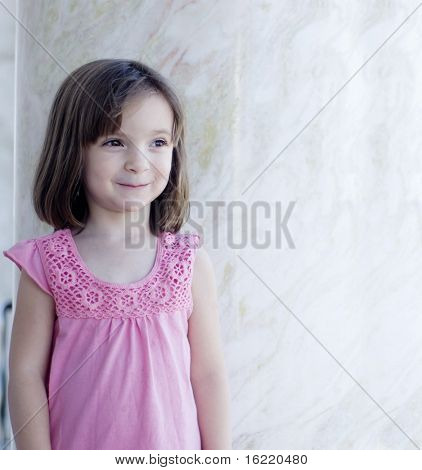 Beautiful little girl with delightful big brown eyes, pink top and sweet smile on her face.