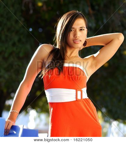 Attractive young multi racial woman swearing orange dress in fashion pose