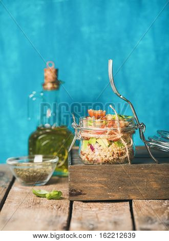 Healthy homemade jar quinoa salad with sun-dried tomatoes, avocado and fresh basil. Detox, dieting, vegetarian, vegan, clean eating food concept. Bright blue background, selective focus, copy space
