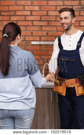 Plumber and woman shaking hands