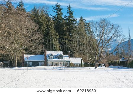 Big farmers house with spacious front yard at winter season. Residential house in snow on a sunny day