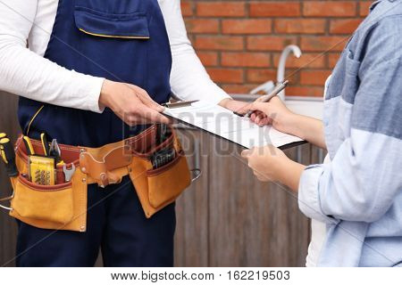 Woman signing receipt for plumber service, closeup