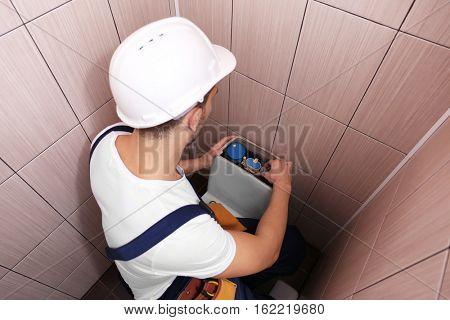 Plumber repairing toilet cistern at water closet