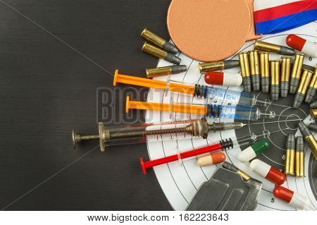 Syringe and medals. Doping in shooting sport. Abuse of anabolic steroids for sports. Deception in biathlon. The International Federation of biathlon - IBU. Ammunition and winners medals.