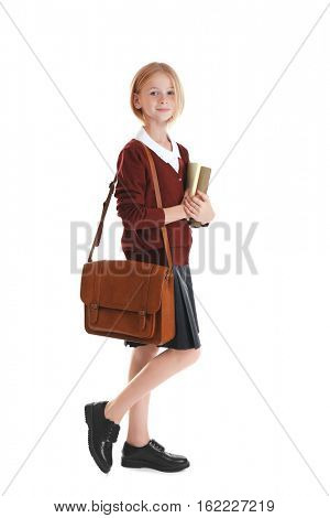 Schoolgirl with books and bag isolated on white
