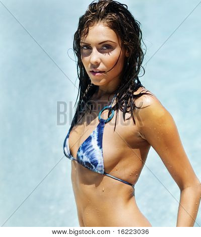 Beautiful young woman enjoying summer vacation swimming in the ocean sea
