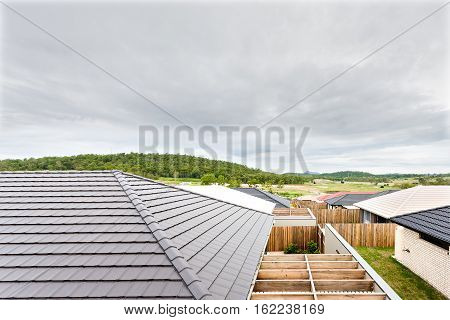 Top view of houses and white or gray color roofs can be seen very clearly and closely. Houses are surrounded by wooden fences and most of the homes have wooden beams Mountains with forest and lawns can be seen in the distance