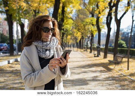 Woman Reading Phone In Autumn Street