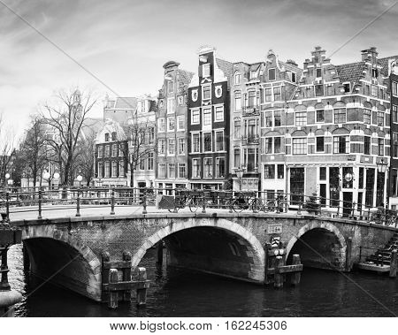 Prinsengracht Canal, Amsterdam, The Netherlands. Typical  Dutch houses  with a crow-stepped gable  behind the bridge.  Black and white.
