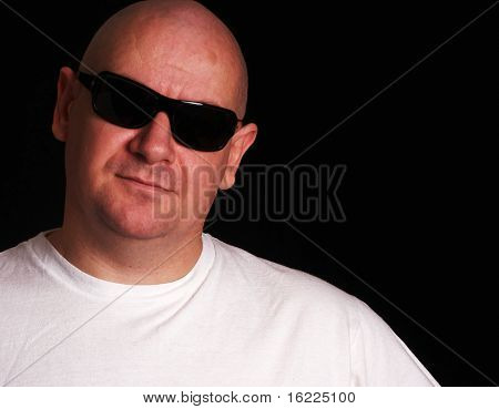 Intimidating looking security bouncer guy with shaved head wearing black sunglasses