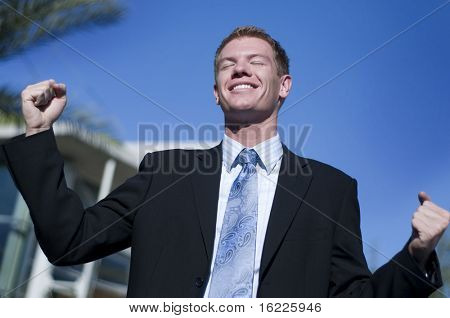 Happy smiling triumphant business man with hands and arm raised to air standing outside corporate head corporate office.