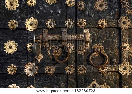 fragment of old church shod iron gate with the modern padlock