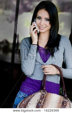 Attractive and cute smiling woman talking on cell phone was holding her bag at a shopping mall.