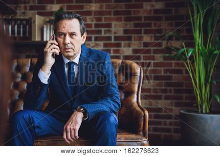 Serious mature male person is sitting on couch. He is speaking on the phone