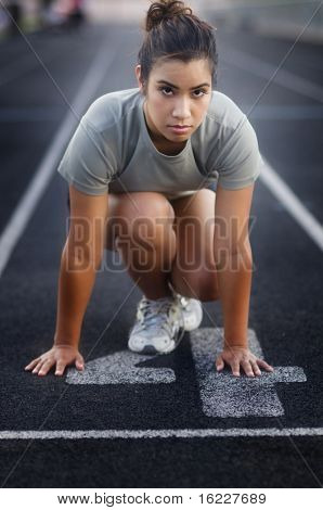 Young woman in start position on running track