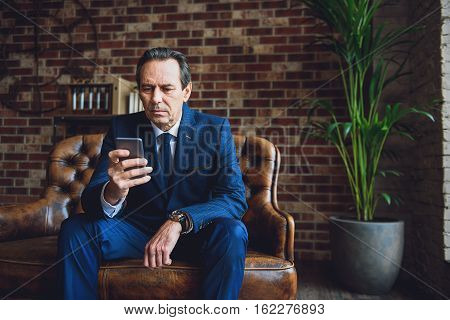 Concentrated matured man is sitting on couch. He absorbedly using his device indoors