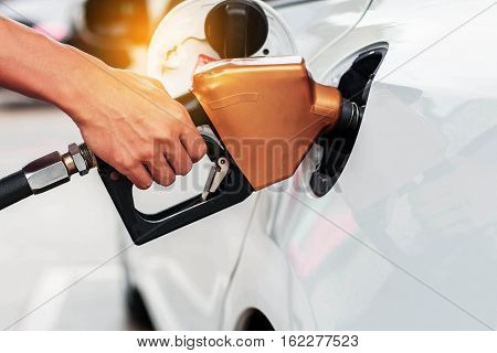 Hands holding a fuel nozzle on cars.