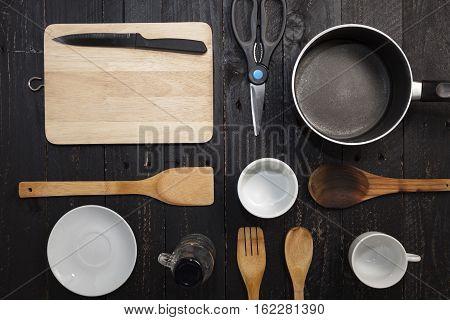 kitchenware on the black wooden background .