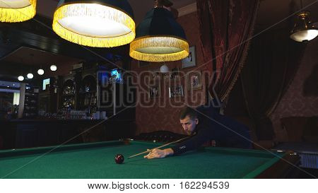 handsome serious man playing pool, a man prepares the cue to play Billiards