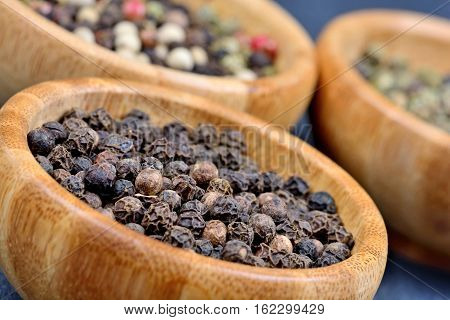 Variation peppercorns in a bamboo bowls on slate