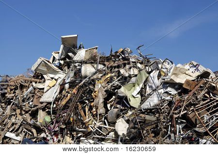 Huge pile of scrap metal junk garbage with blue sky background