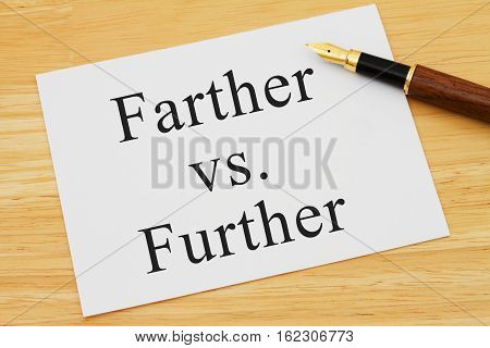 Learning to use proper grammar A white card on a desk with a pen with words Farther vs Further