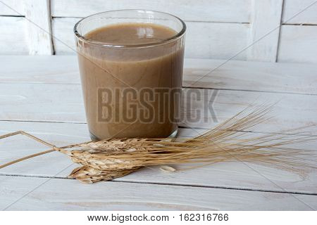 Traditional Drink from Balkan Peninsula Boza (fermented cereal beverage) and wheat over white wooden background