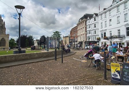 EXETER UK 11 July 2016: people sitting at the tables at an outdoor cafe on the square Cathedral Green. Exeter. Devon. UK