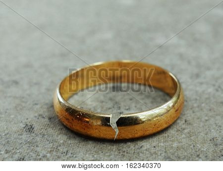 Cracked gold wedding ring -- divorce or infidelity concept