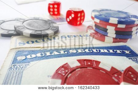 Social Security cards with dice and poker chips