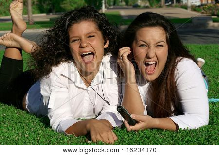 2 girls laughing while listening to music