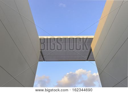 Abstract minimalistic composition of ultra-modern architecture. A partial view of an horizontal beam on walls against sky background.