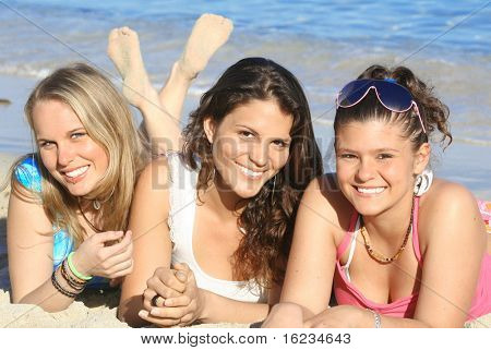 3 young women relaxing on beach