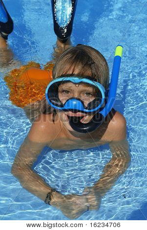 Young boy playing in water with flippers ,snorkel and mask