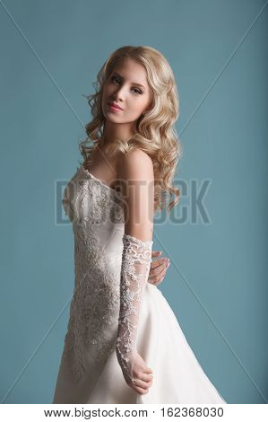 Young beautiful bride in magnificent wedding dress posing at studio on blue background