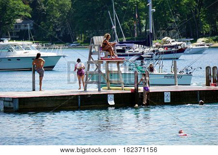 HARBOR SPRINGS, MICHIGAN / UNITED STATES - AUGUST 3, 2016: A girl climbs onto the raft at the Zorn Park Public Beach near downtown Harbor Springs.