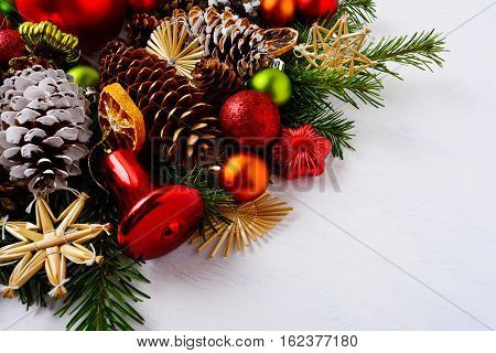 Christmas decoration with dried orange slices red jingle bell and star. Christmas greeting background with fir branches and pine cones. Copy space.