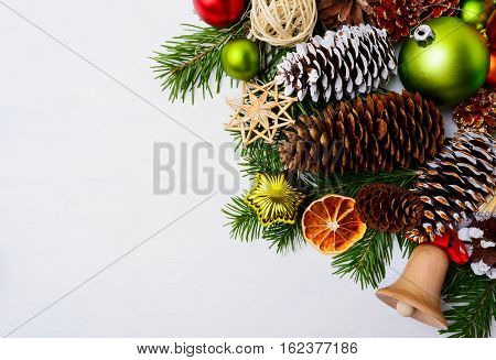 Christmas decoration with wooden jingle bell and straw ornaments. Christmas greeting background with fir branches and pine cones. Copy space.