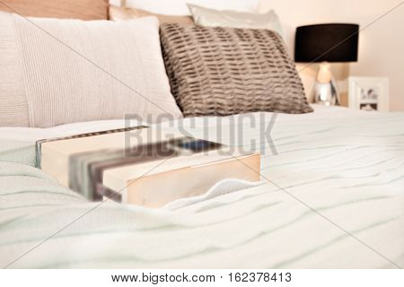 Novel on the bed in front of the pillows the book is probably a novel there is a lamp can be seen corner of the room near to the pillows on the bed. The background is blurred and focusing on the book