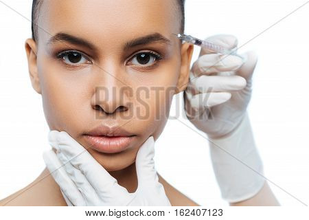 Forever young. Concentrated involved young Negroid woman standing against white background and expressing concentration while receiving the injection in her face