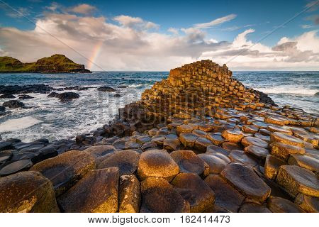 Sunrise view at Irish giant causeway vulcanic formation with rainbow nearby