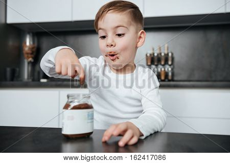 Picture of cute little boy standing in the kitchen while eating sweeties. Look at sweeties.