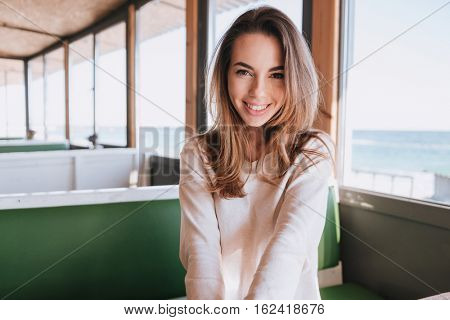 Happy shy Woman sitting by the table in cafe near the sea and looking at camera