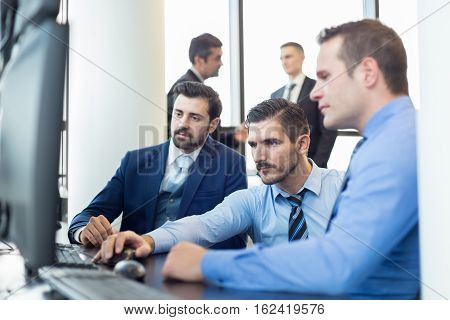 Business team working in corporate office. Businessmen trading stocks. Stock traders looking at graphs, indexes and numbers on multiple computer screens. Business success concept.