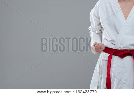 Cropped photo of young sportsman dressed in kimono practice in karate isolated over grey background.
